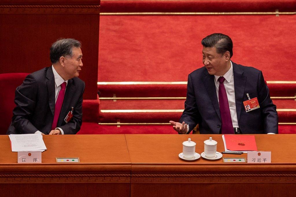 Le président chinois Xi Jinping et Wang Yang discutent lors de la séance de clôture de l'Assemblée populaire nationale au Grand Palais du Peuple à Pékin le 11 mars 2021.