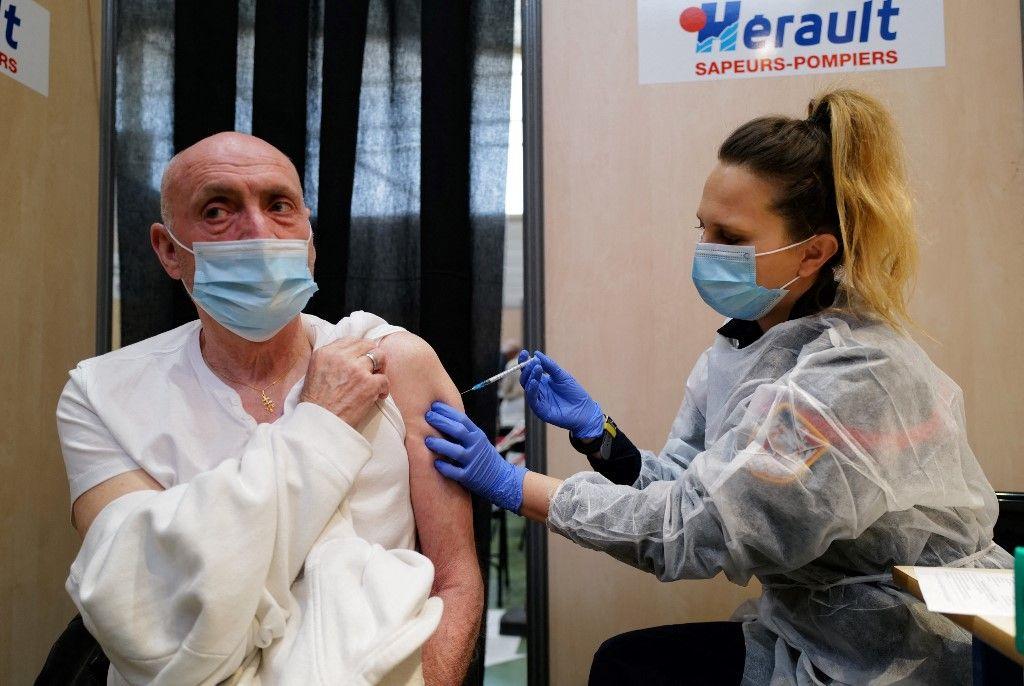 Une pompier injecte à un homme une dose de vaccin contre Covid-19 à Vailhauques, dans le département de l'Hérault, en mars 2021.
