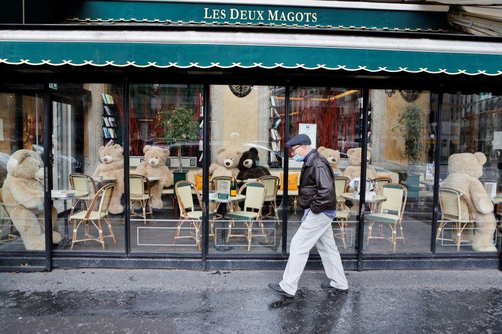 Un homme portant un masque de protection passe devant la brasserie emblématique Les Deux Magots, fermée et décorée d'ours en peluche assis à des tables, en janvier 2021.