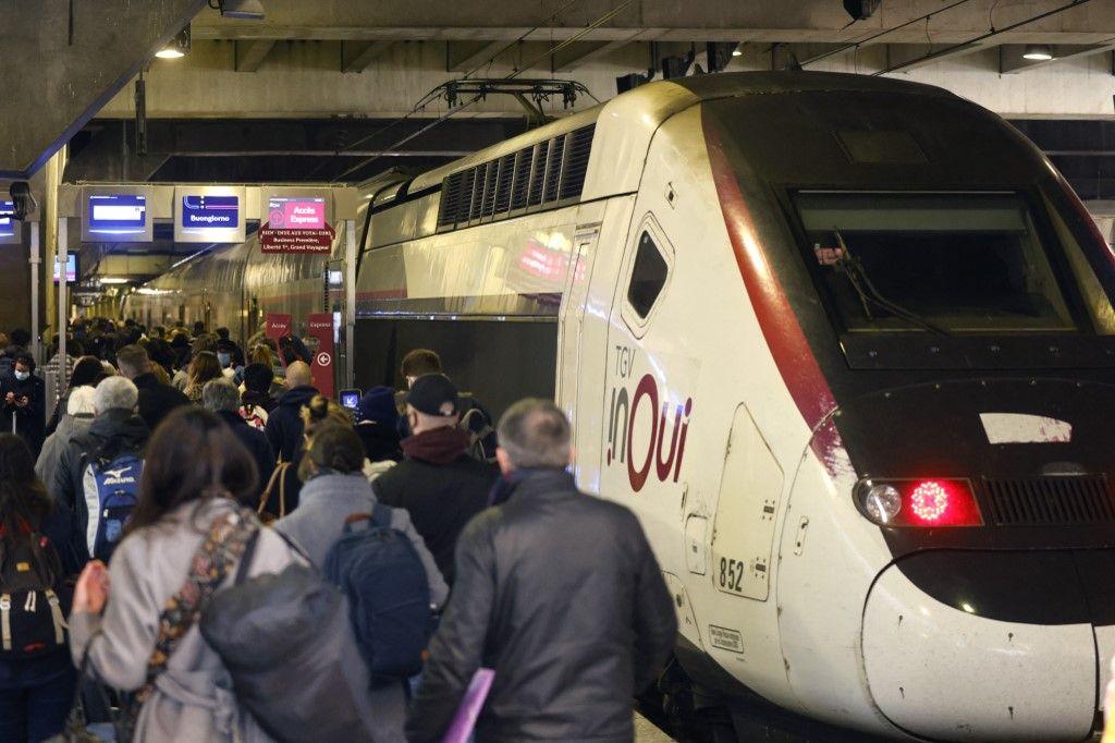 Des voyageurs marchent le long d'un quai pour prendre un train au départ de la gare Montparnasse, à Paris le 19 mars 2021.