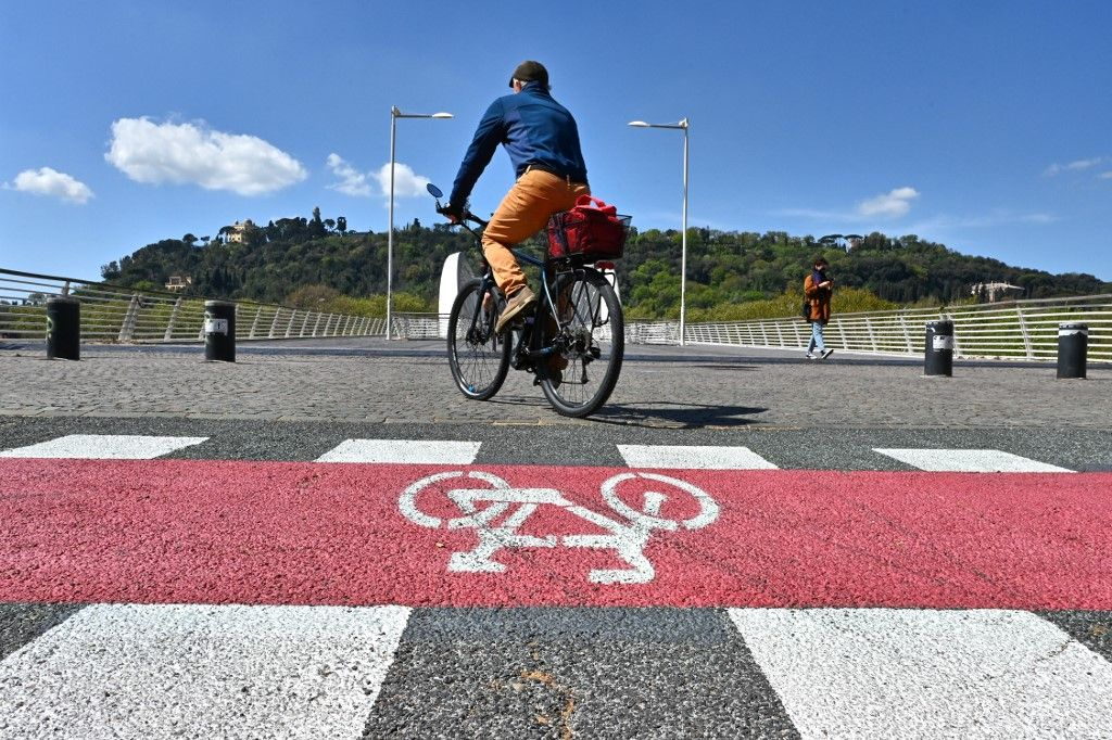 Un homme traverse à vélo une piste cyclable au pont Ponte della Musica, le 9 avril 2021, à Rome.