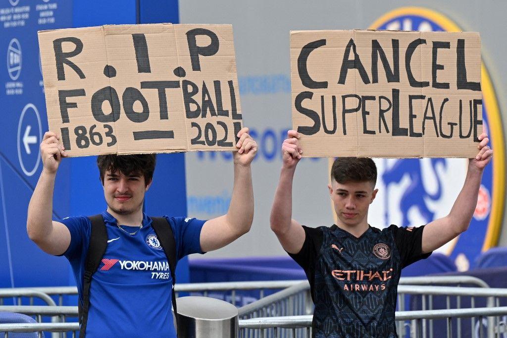 Des fans de football brandissent des pancartes contre l'idée d'une nouvelle Super Ligue européenne devant le stade Stamford Bridge du club de Premier League de Chelsea à Londres en avril 2021.