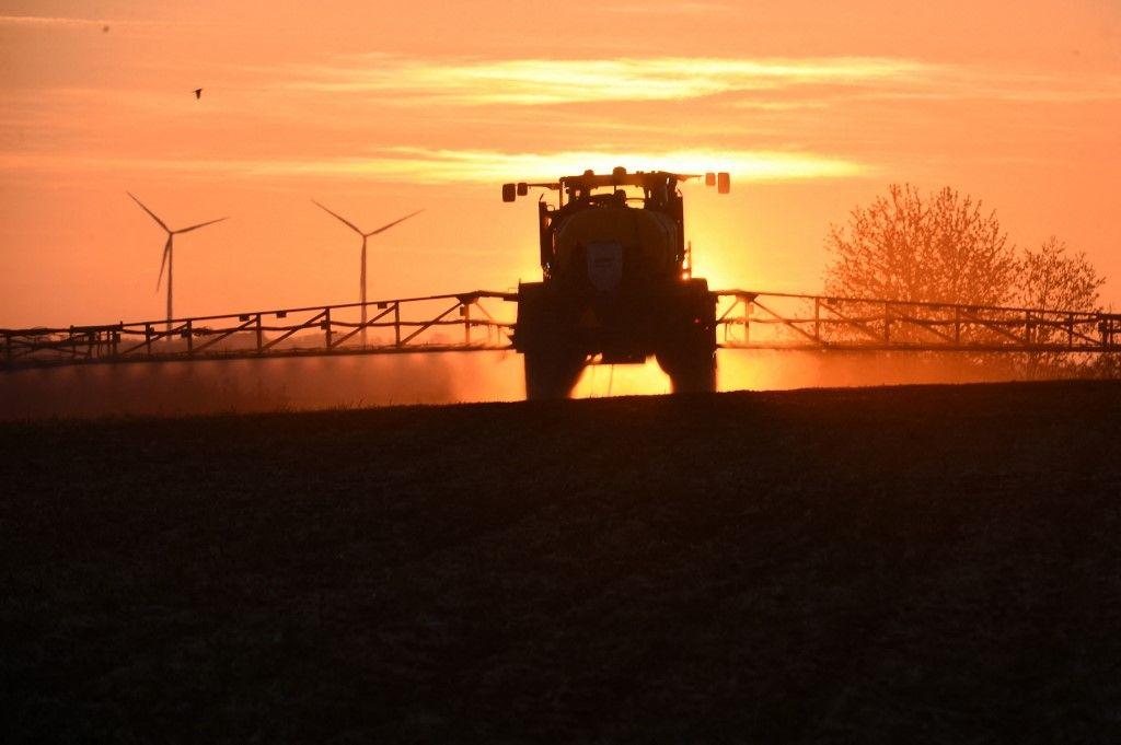 """Le soleil se lève alors qu'un agriculteur pulvérise l'herbicide au glyphosate """"Roundup 720"""", dans le nord-ouest de la France, dans un champ de maïs, près d'un parc éolien, le 23 avril 2021."""