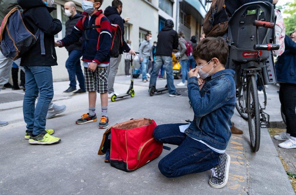 Un garçon ajuste son masque protecteur avant d'entrer dans son école primaire, à Paris, le 26 avril 2021.