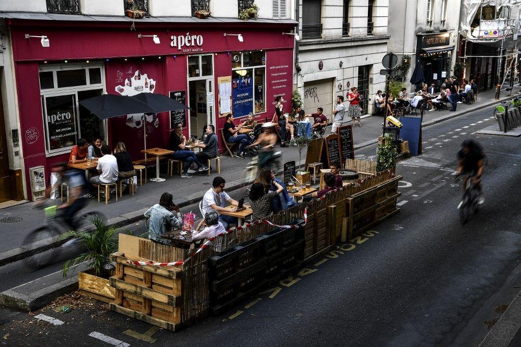 Des gens prennent un verre à la terrasse d'un café à Paris en juillet 2020 en respectant la distanciation sociale liée à la pandémie de Covid-19.