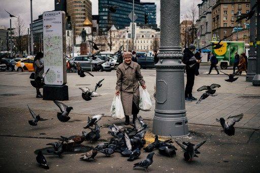 Une personne âgée s'amuse face à des pigeons, à Moscou.