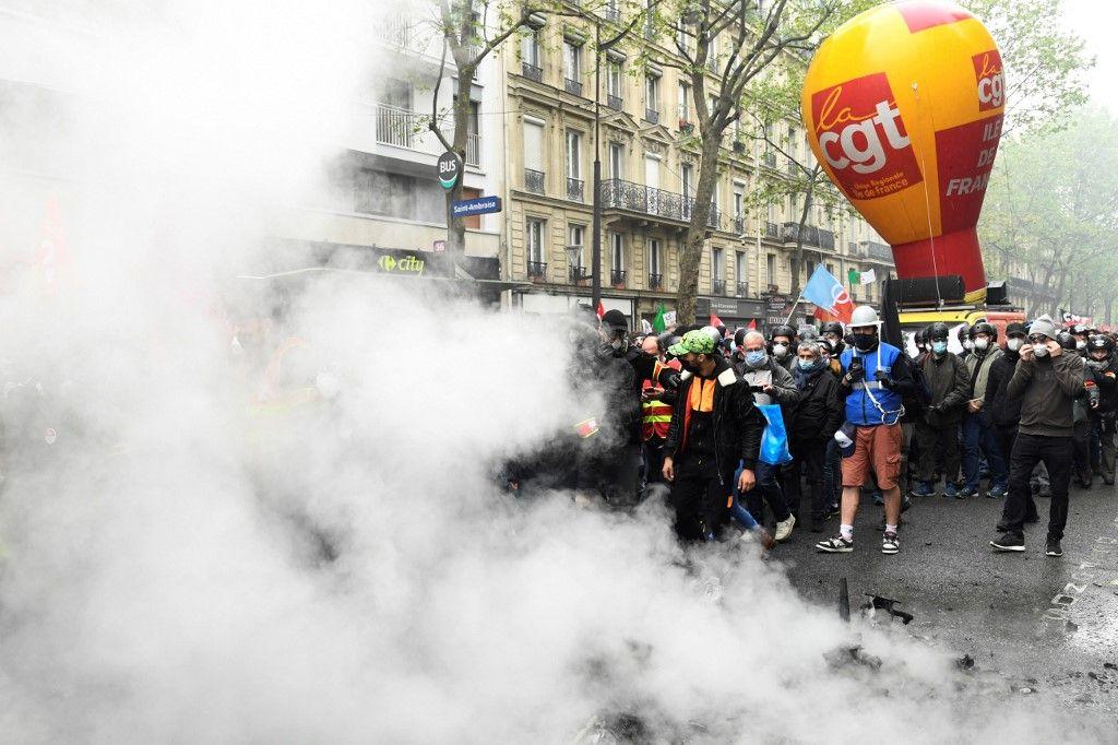 Les membres du syndicat français de la CGT reprennent leur marche après une interruption en raison d'affrontements entre manifestants et policiers lors des manifestations du 1er mai à Paris le 1er mai 2021.