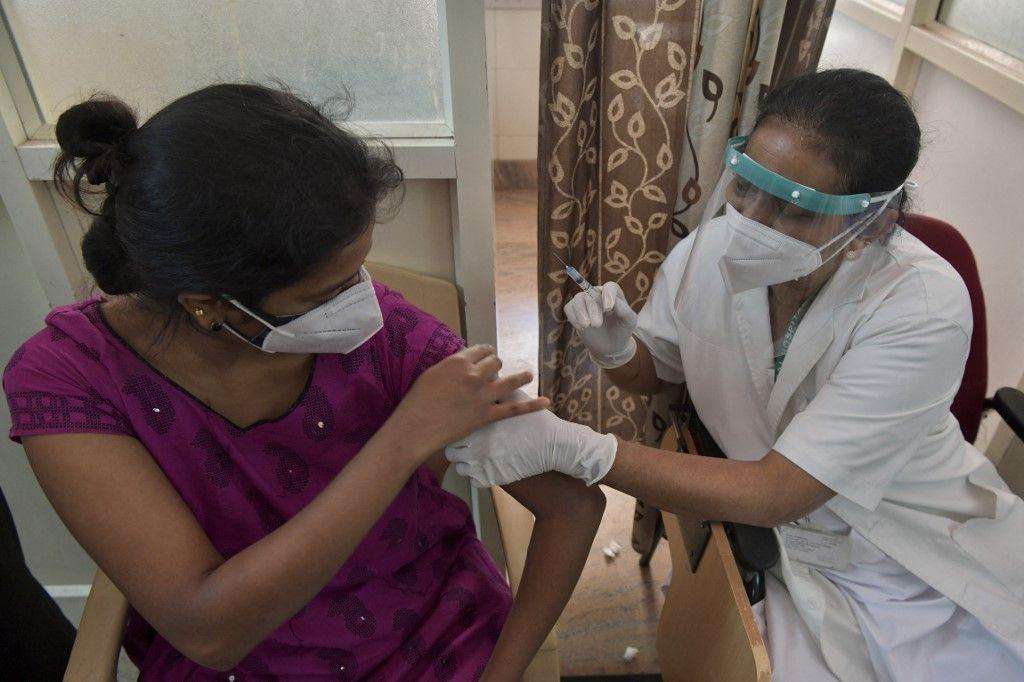 Une travailleuse médicale inocule à une femme une dose du vaccin contre la Covid-19 dans un centre de vaccination d'un hôpital de Bangalore le 7 mai 2021.