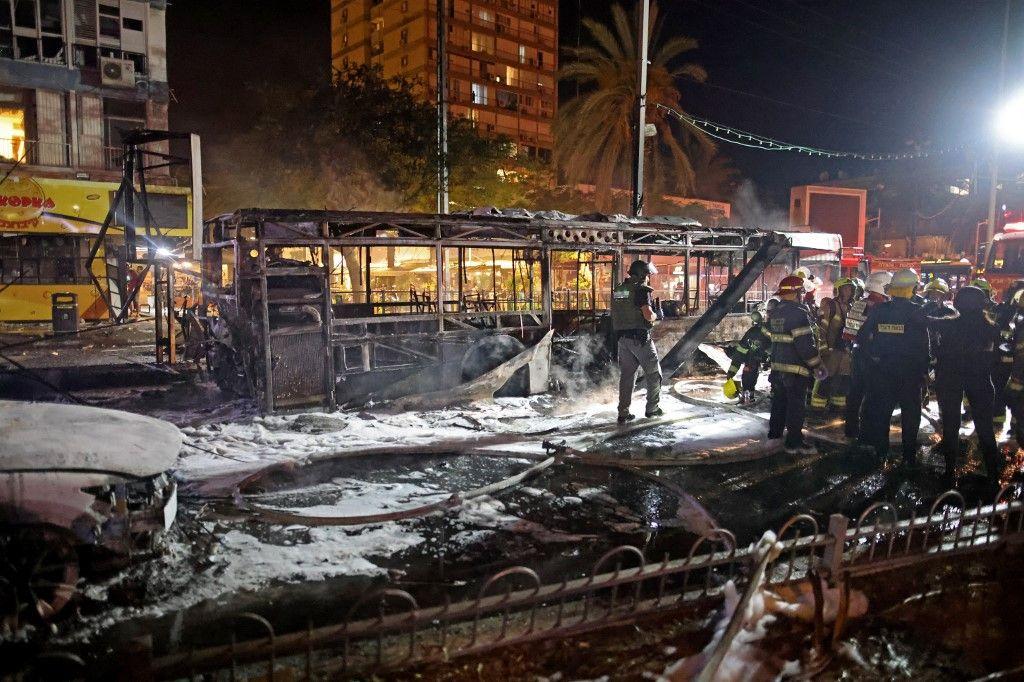 Les pompiers israéliens vérifient un bus incendié dans la ville israélienne de Holon, près de Tel Aviv, le 11 mai 2021, après que des roquettes ont été lancées vers Israël depuis la bande de Gaza contrôlée par le mouvement palestinien Hamas.