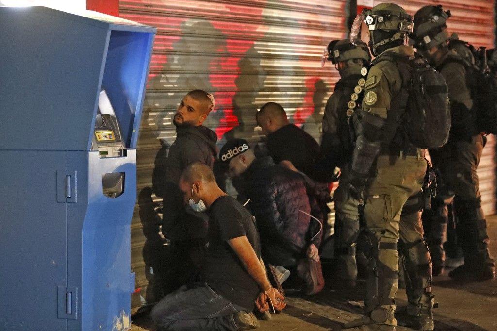Les forces israéliennes arrêtent un groupe d'Arabes israéliens dans la ville mixte judéo-arabe de Lod le 13 mai 2021 lors d'affrontements.
