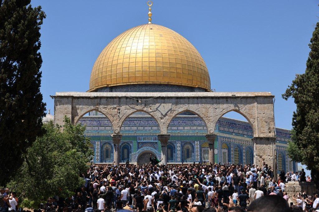 Des fidèles musulmans palestiniens écoutent les slogans d'un homme tenant le drapeau du Hamas dans l'enceinte de la mosquée al-Aqsa, le 14 mai 2021.