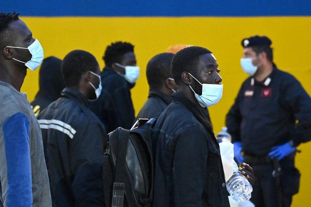 Des migrants sur l'île italienne de Lampedusa avec un responsable de la sécurité, le 14 mai 2021, alors qu'ils se préparent à monter à bord d'un navire à destination d'une ville sicilienne.