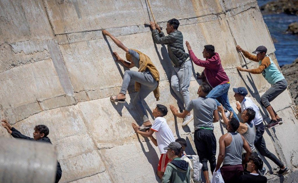 Des migrants escaladent une digue dans la ville du nord après avoir tenté de traverser la frontière entre le Maroc et l'enclave nord-africaine espagnole de Ceuta le 19 mai 2021.
