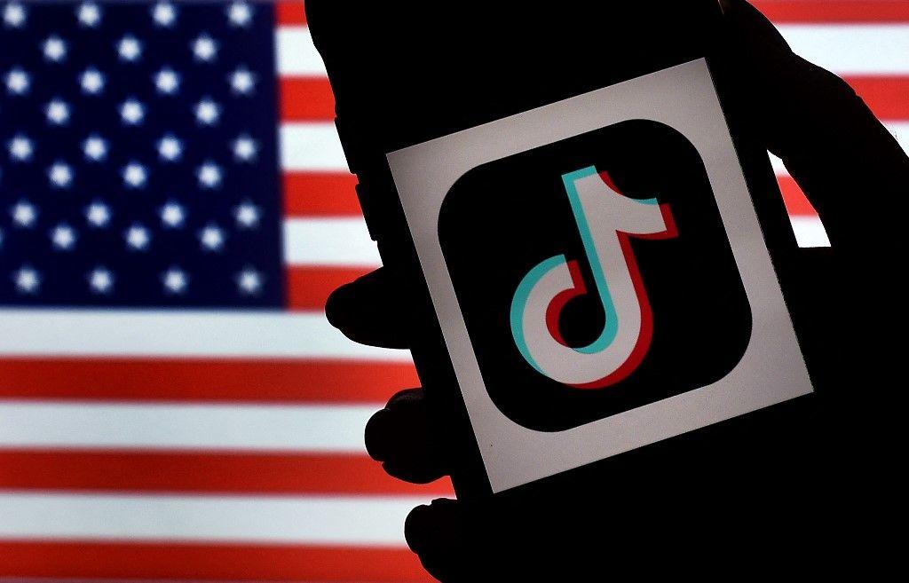 Le logo de l'application TikTok est affiché sur l'écran d'un iPhone avec en fond de drapeau américain le 3 août 2020 à Arlington, en Virginie.