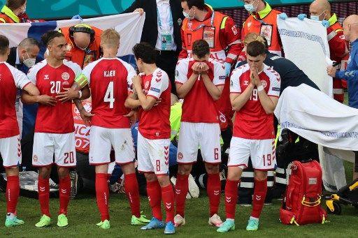 Des joueurs de l'équipe danoise protègent leur coéquipier des regards, pendant que des soignants lui prodiguent les premiers soins.