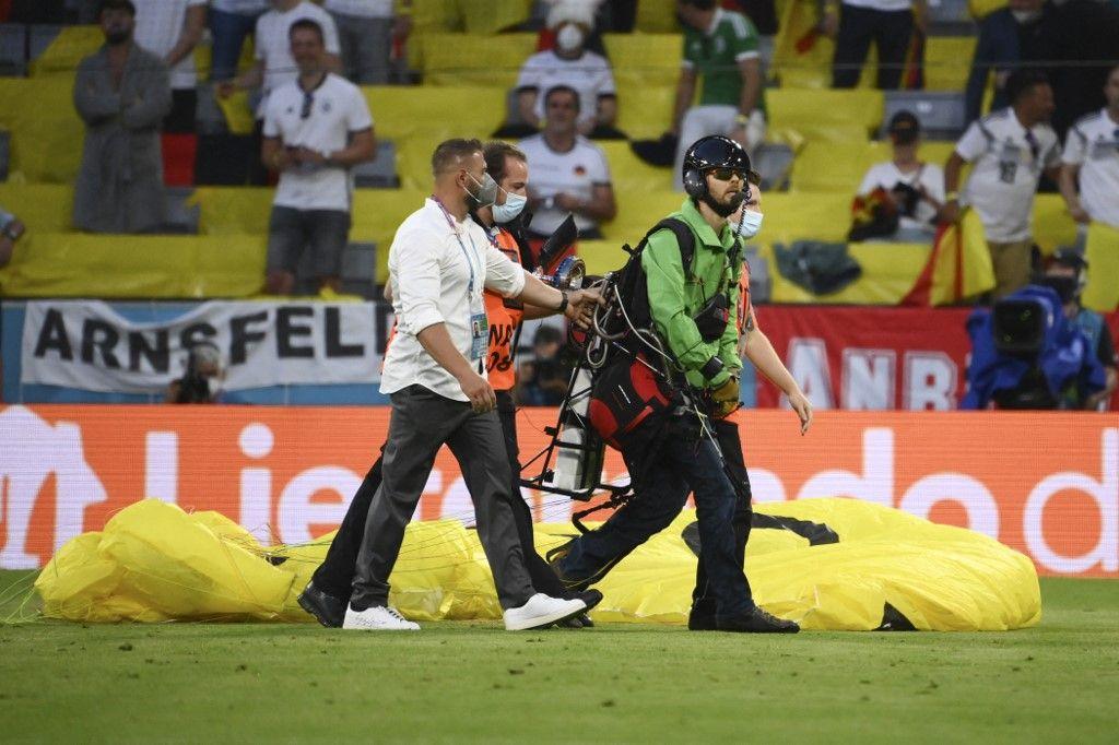 Un pilote d'ULM, qui a pénétré à l'intérieur du stade de Munich avec un message de Greenpeace, est escorté par la sécurité après avoir atterri sur le terrain avant France – Allemagne.