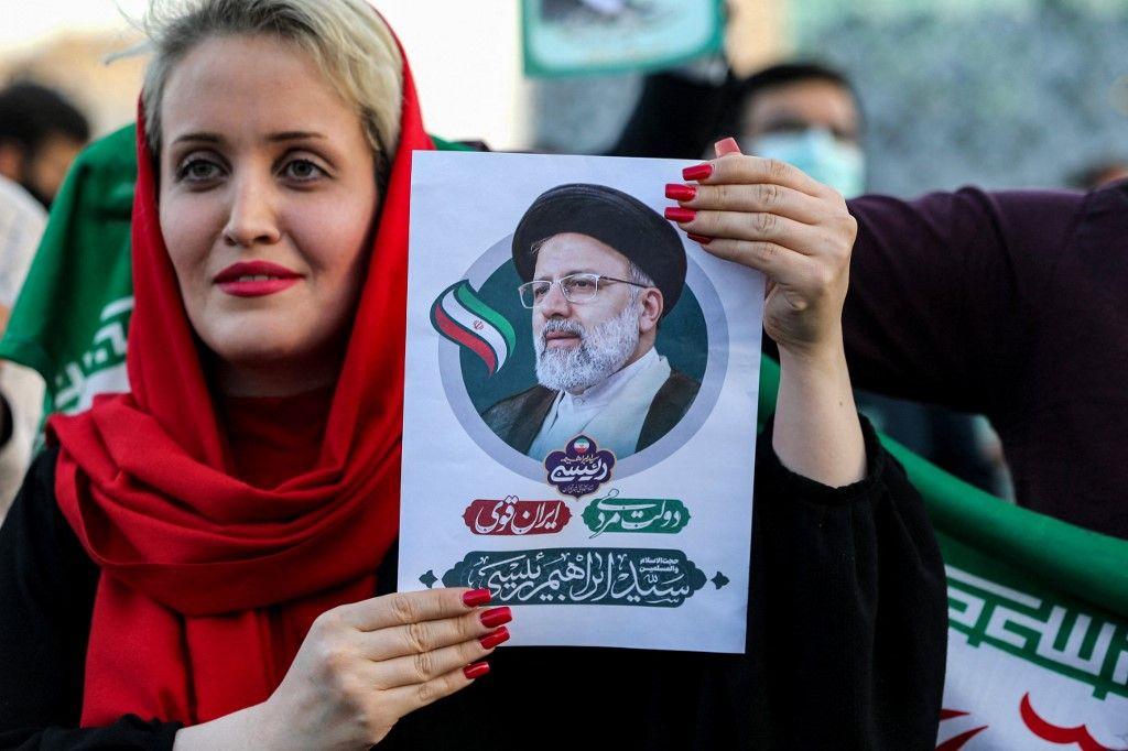 Une femme tient une photo du président iranien élu Ebrahim Raïssi alors que ses partisans célèbrent sa victoire place Imam Hussein dans la capitale Téhéran le 19 juin 2021.