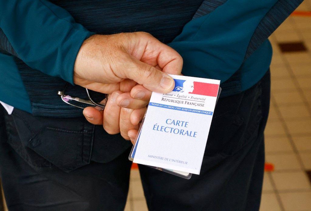 Un électeur attend avec sa carte électorale pour voter dans un bureau de vote dans le nord de la France pour le premier tour des élections régionales françaises le 20 juin 2021.