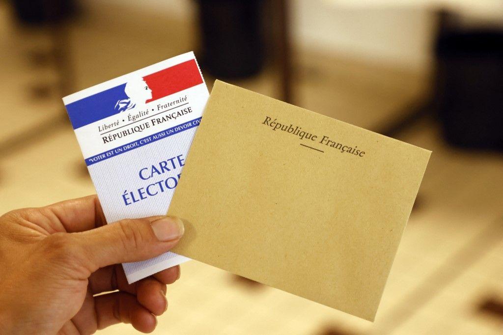 Un électeur muni de sa carte dans un bureau de vote dans le nord de la France, pour le premier tour de l'élection régionale française, le 20 juin 2021.