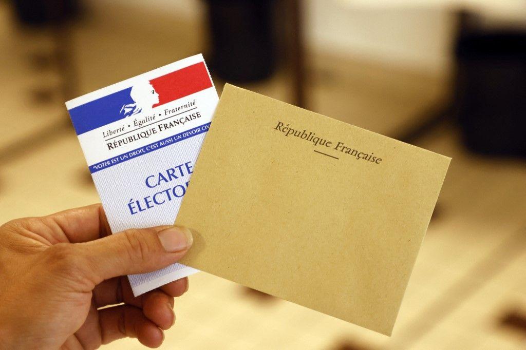 Un électeur présente sa carte électorale et son enveloppe électorale dans un bureau de vote dans le nord de la France, pour le premier tour des élections régionales françaises le 20 juin 2021.