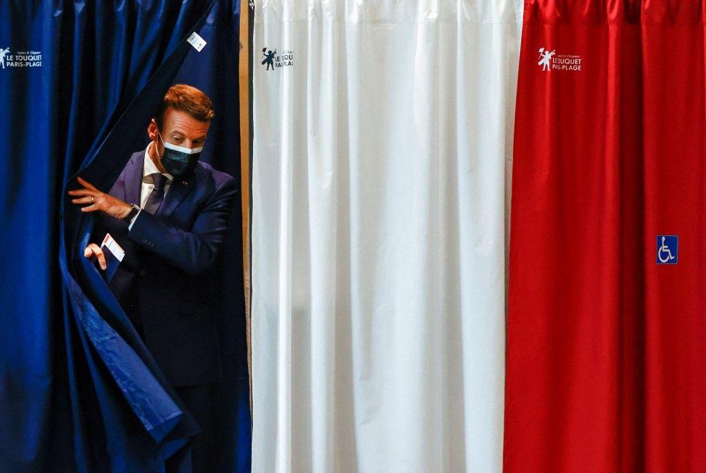 Le président Emmanuel Macron quitte l'isoloir avant de voter au Touquet, pour le premier tour des élections régionales, le 20 juin 2021.