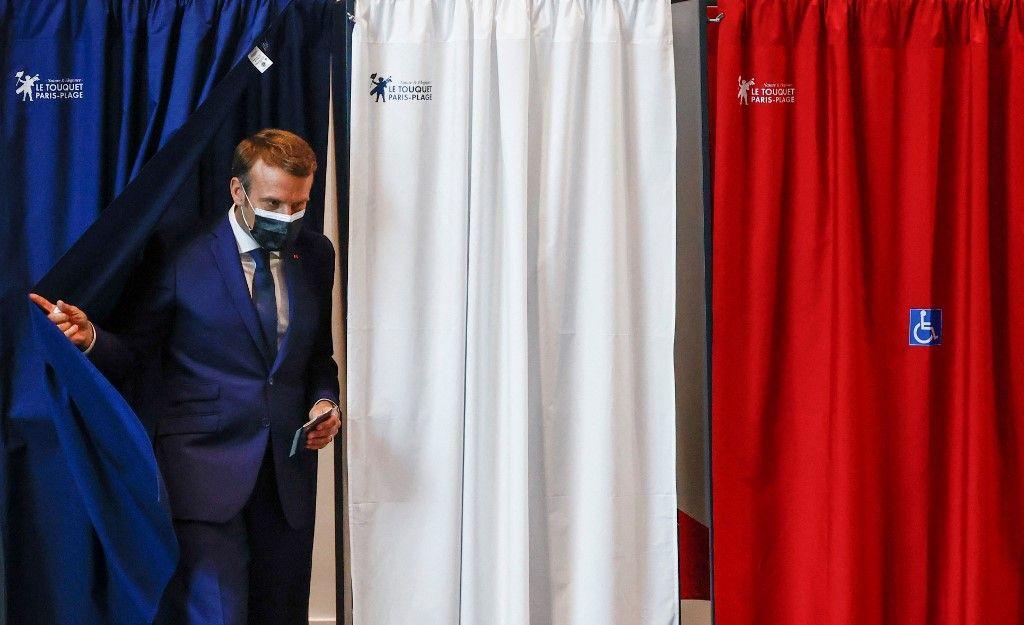Le président emmanuel Macron quitte l'isoloir avant de voter au bureau de vote du Touquet, pour le premier tour des élections régionales françaises le 20 juin 2021.