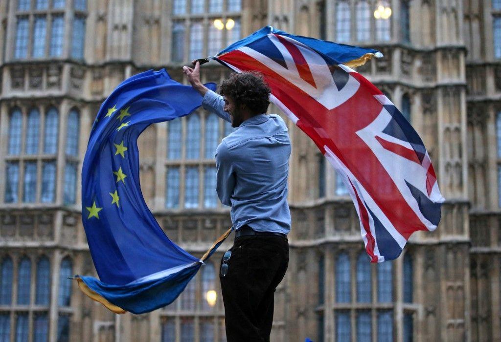 Un homme brandit à la fois un drapeau du Royaume-Uni et un drapeau européen devant le Parlement britannique lors d'une manifestation dans le centre de Londres, le 28 juin 2016.