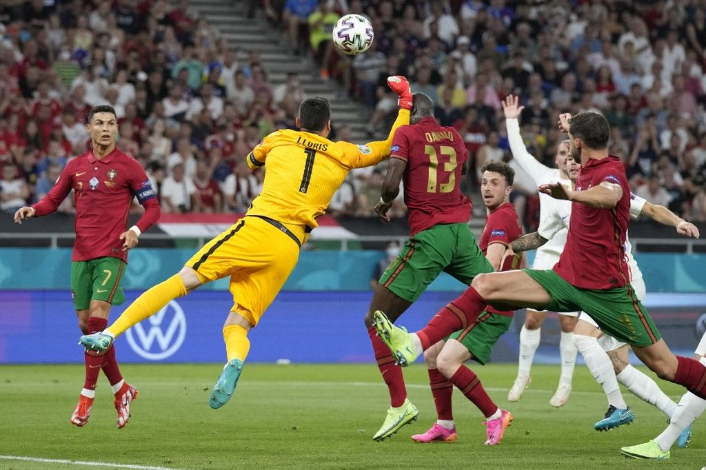 Le gardien de but français Hugo Lloris commet une faute sur le milieu de terrain portugais Danilo Pereira lors du match de l'UEFA EURO 2020 entre le Portugal et la France à Budapest, le 23 juin 2021.