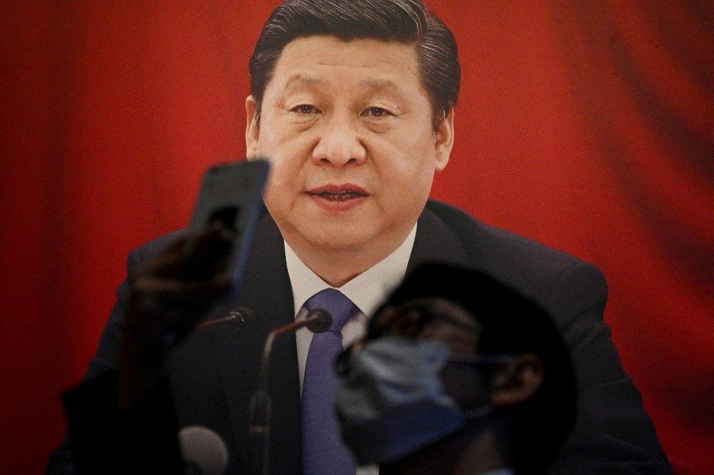 Un journaliste utilise son téléphone devant une photo du président chinois Xi Jinping, lors d'une visite au Musée du Parti communiste de Chine, le 25 juin 2021.