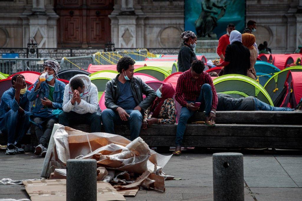Des migrants sans-abri sont assis sur un banc à côté de tentes lors d'une action de l'association Utopia56 devant l'hôtel de ville de Paris, le 25 juin 2021, pour mettre en lumière le sort des sans-abri.
