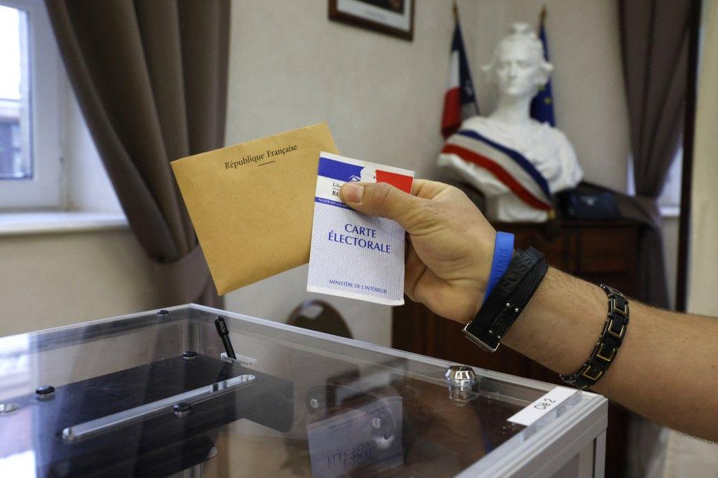 Une personne avec une carte électorale et un bulletin de vote avant de voter dans le nord de la France, pour le second tour des élections régionales, le 27 juin 2021.