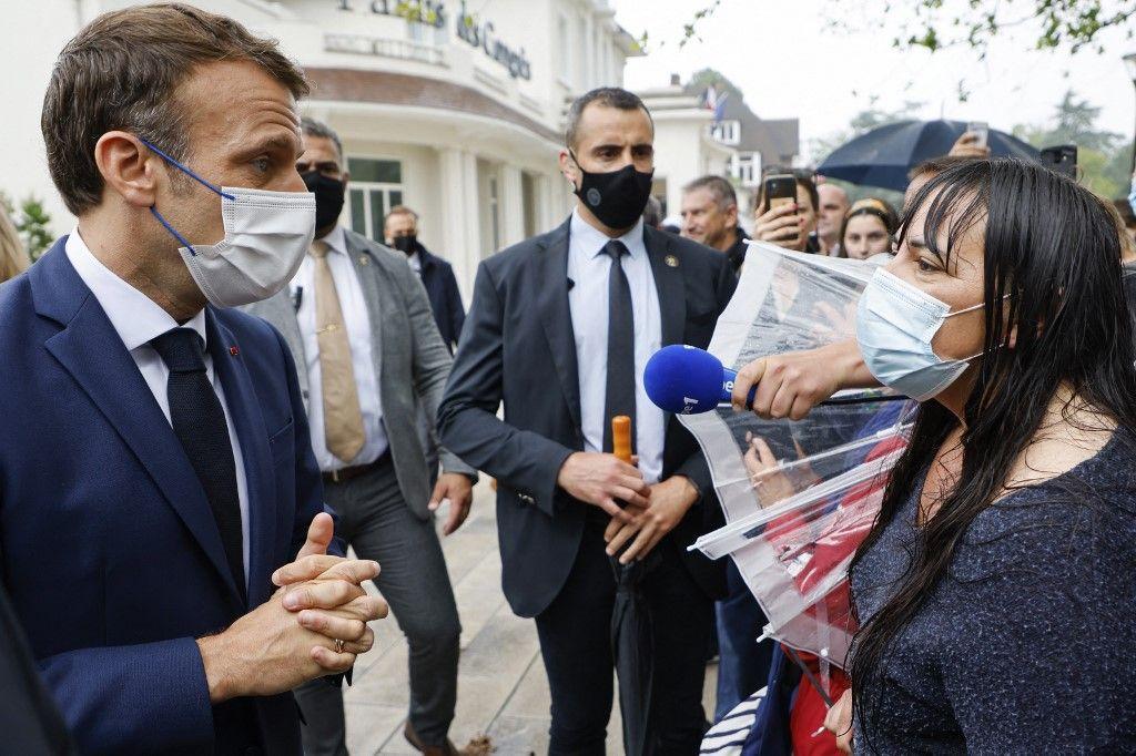 Le président Emmanuel Macron s'entretient avec une femme alors qu'il salue les riverains après avoir voté dans un bureau de vote du Touquet, pour le second tour des élections régionales, le 27 juin 2021.