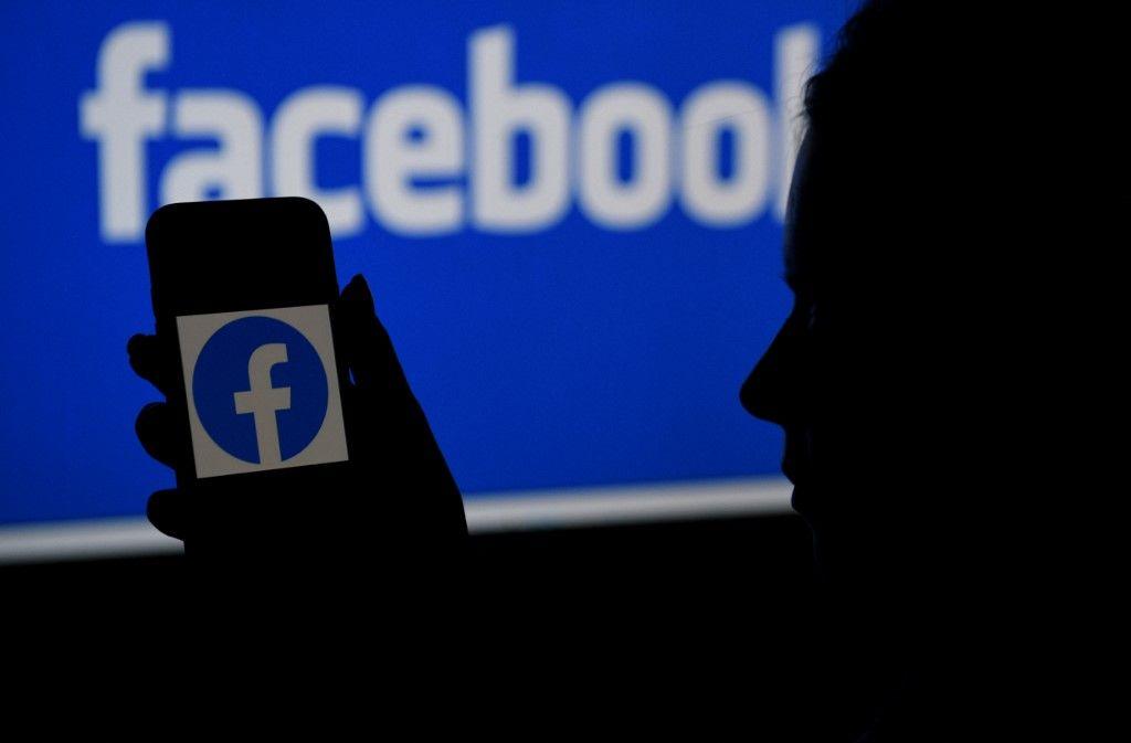 Dans cette photo d'illustration prise le 7 avril 2021, un écran de téléphone affiche le logo de Facebook sur un arrière-plan de site Web Facebook, à Arlington, en Virginie.