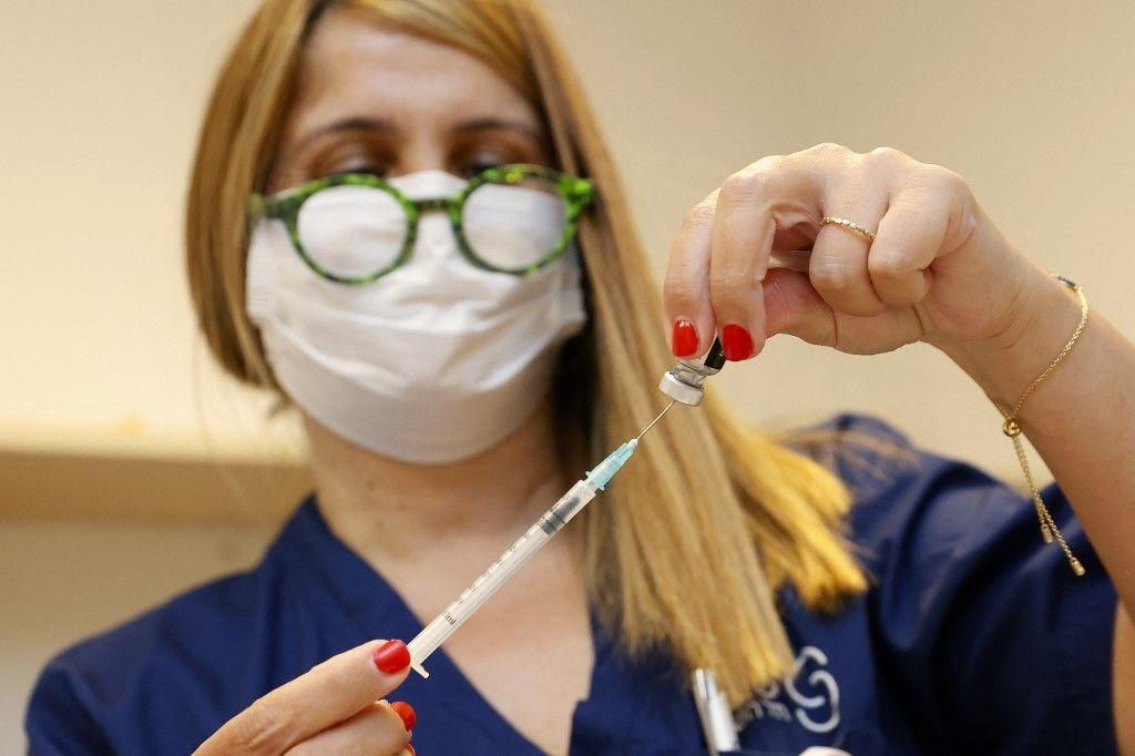 Une travailleuse médicale prépare une injection du vaccin Pfizer-BioNTech contre la Covid-19 à administrer en troisième dose, près de Tel Aviv, en Israël, le 12 juillet 2021