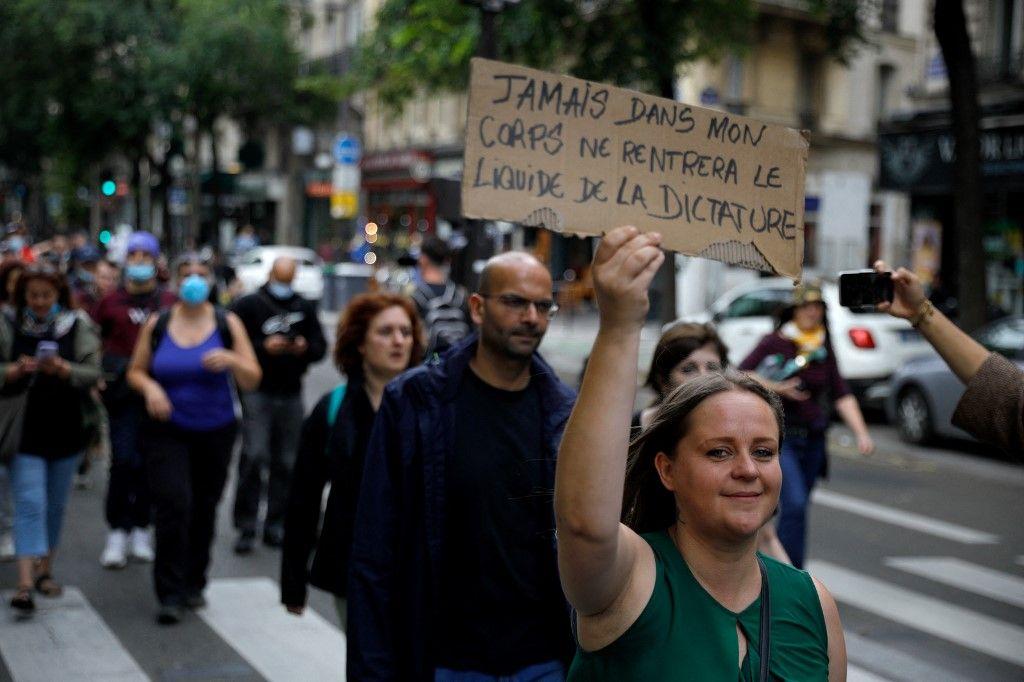 Une femme tient une pancarte lors d'un rassemblement dans le centre de Paris le 14 juillet 2021 pour protester contre une décision gouvernementale concernant l'extension du pass sanitaire dans la lutte contre la Covid-19.