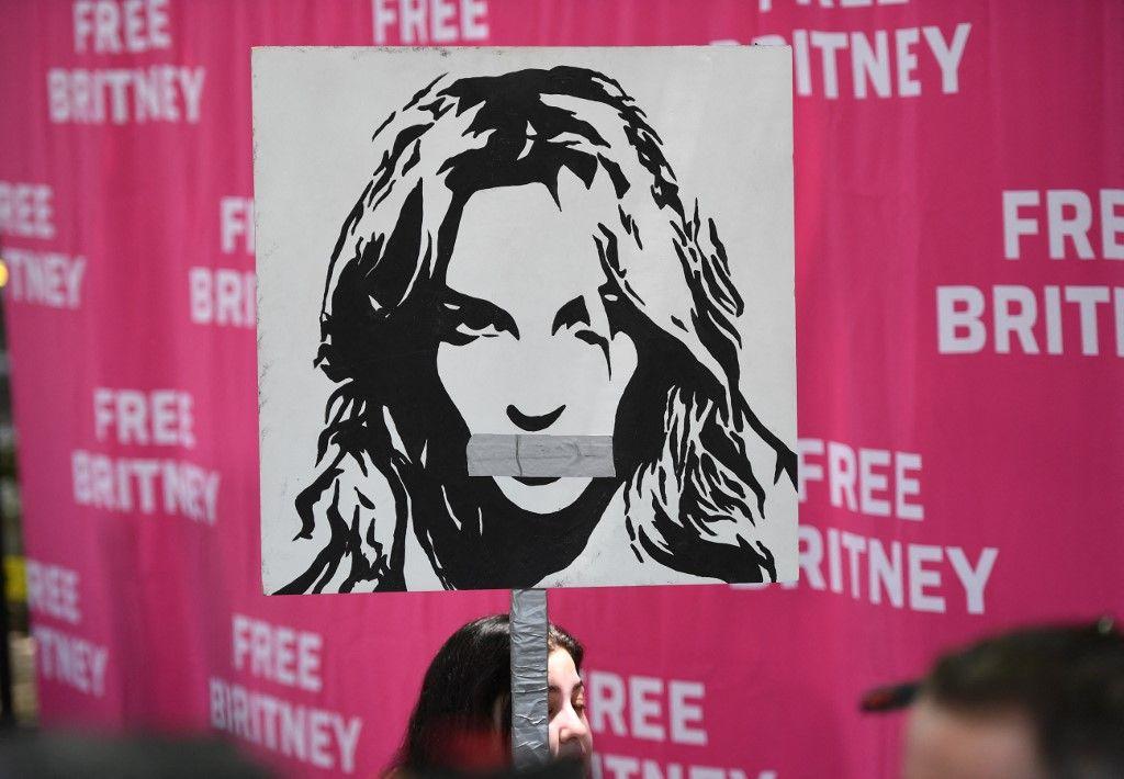 Une femme tient une affiche de Britney Spears, la bouche fermée, alors que les fans se rassemblent devant le palais de justice du comté de Los Angeles le 14 juillet 2021, lors d'une audience prévue dans l'affaire de tutelle de Britney Spears.