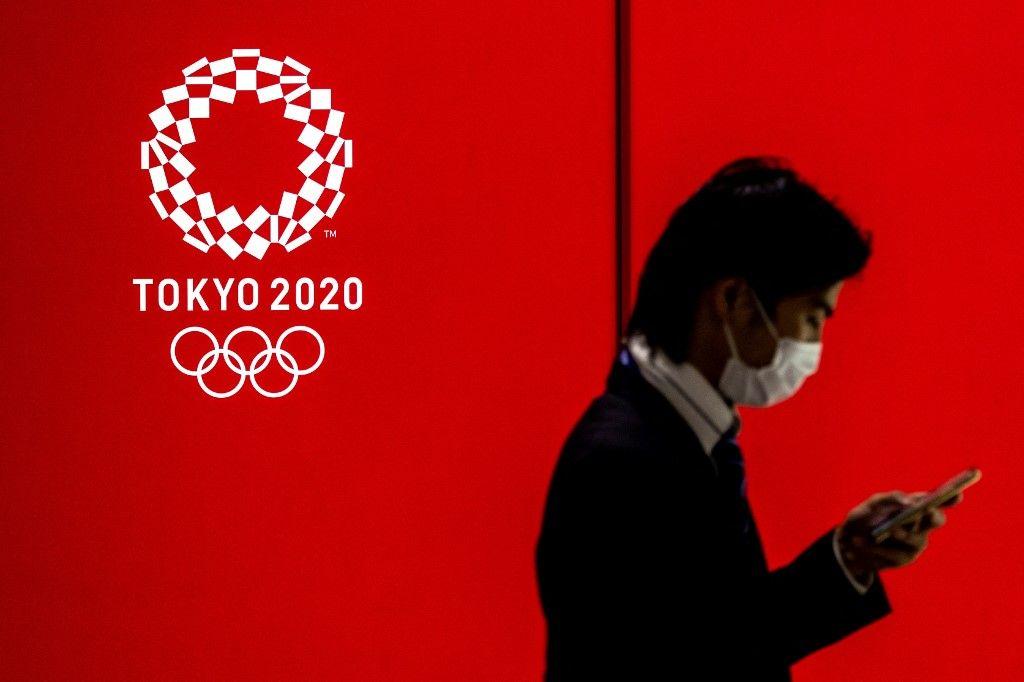 Un homme passe devant un logo des Jeux Olympiques de Tokyo 2020 à Tokyo le 15 juillet 2021.