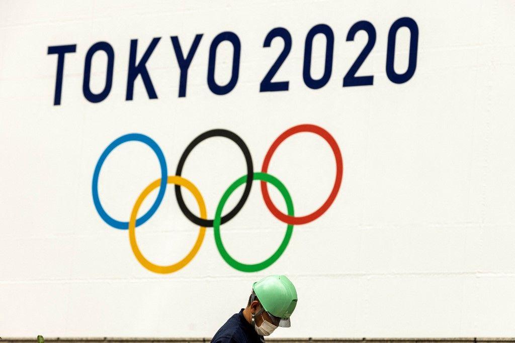 Un ouvrier portant un masque travaille sous un logo des Jeux olympiques de Tokyo 2020 à Tokyo, le 15 juillet 2021.