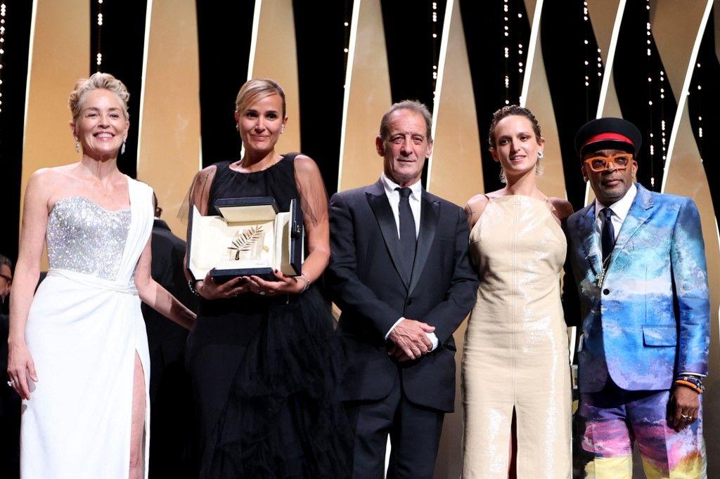 """La réalisatrice française Julia Ducournau pose sur scène avec Sharon Stone, Vincent Lindon, Agathe Rousselle et Spike Lee après avoir remporté la Palme d'Or pour son film """"Titane"""" lors de la 74e édition du Festival de Cannes."""