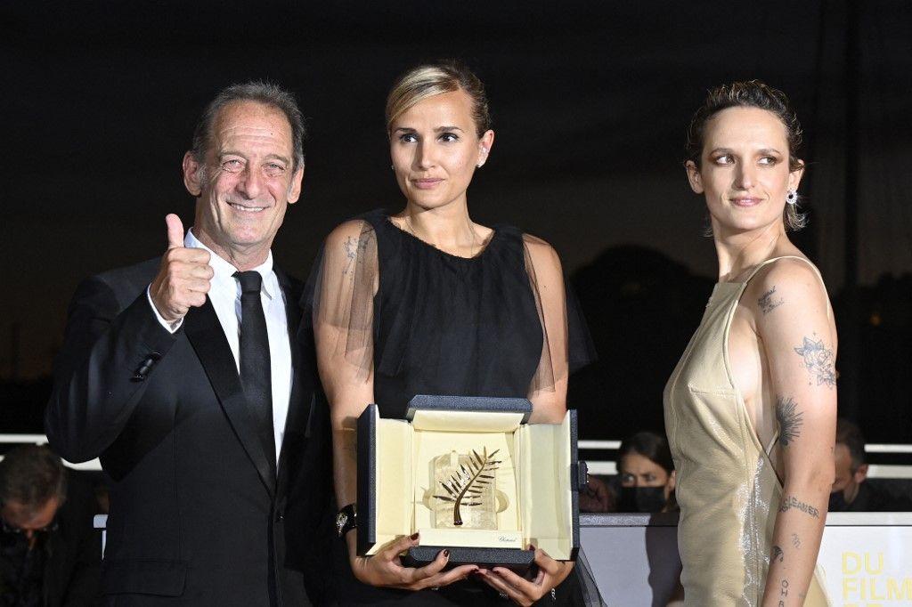 Julia Ducournau pose avec l'acteur Vincent Lindon et l'actrice Agathe Rousselle, après avoir remporté la Palme d'Or pour Titane.