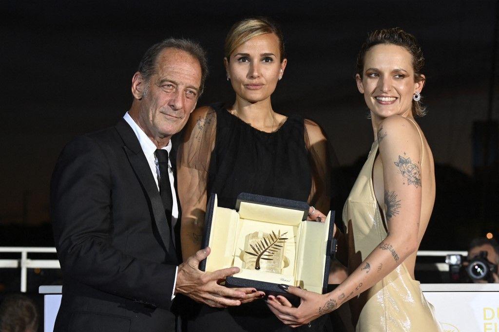 """La réalisatrice française Julia Ducournau pose avec le trophée de la Palme d'Or aux côtés de Vincent Lindon et Agathe Rousselle lors d'un photocall après le sacre de """"Titane"""" lors de la cérémonie de clôture du Festival de Cannes, le 17 juillet 2021."""