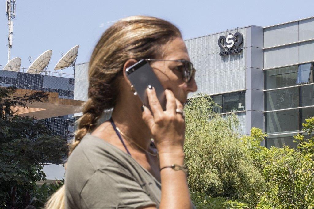 Une femme utilise son iPhone devant le bâtiment abritant le groupe israélien NSO, à Herzliya, près de Tel Aviv. Cette entreprise israélienne est accusée d'avoir fourni des logiciels espions Pegasus aux gouvernements.