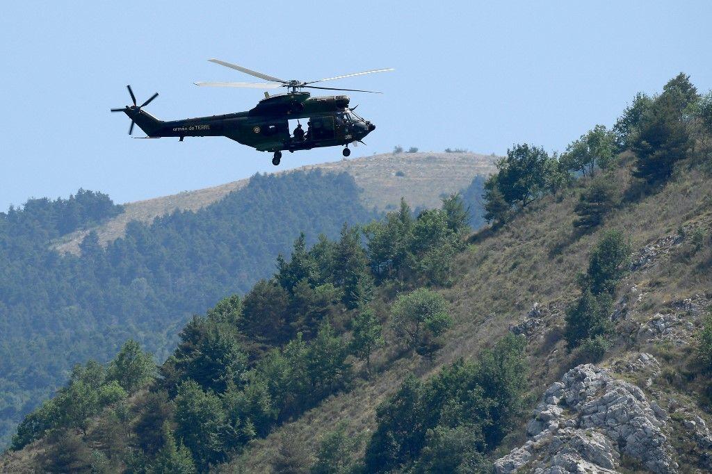 Un hélicoptère Puma de l'Armée de Terre française survole Gréolières, dans le sud-est de la France, le 19 juillet 2021, à la recherche d'un homme soupçonné du meurtre d'une femme.