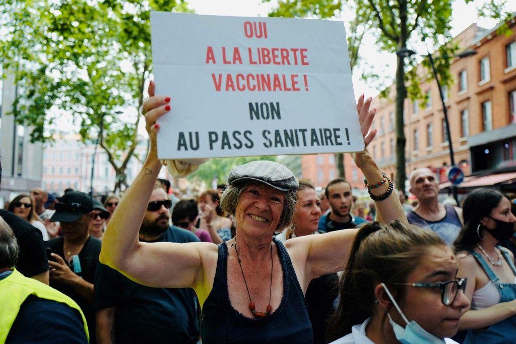 Une manifestante brandit une pancarte lors d'un rassemblement contre la vaccination et le passe sanitaire, à Toulouse, le 24 juillet 2021.