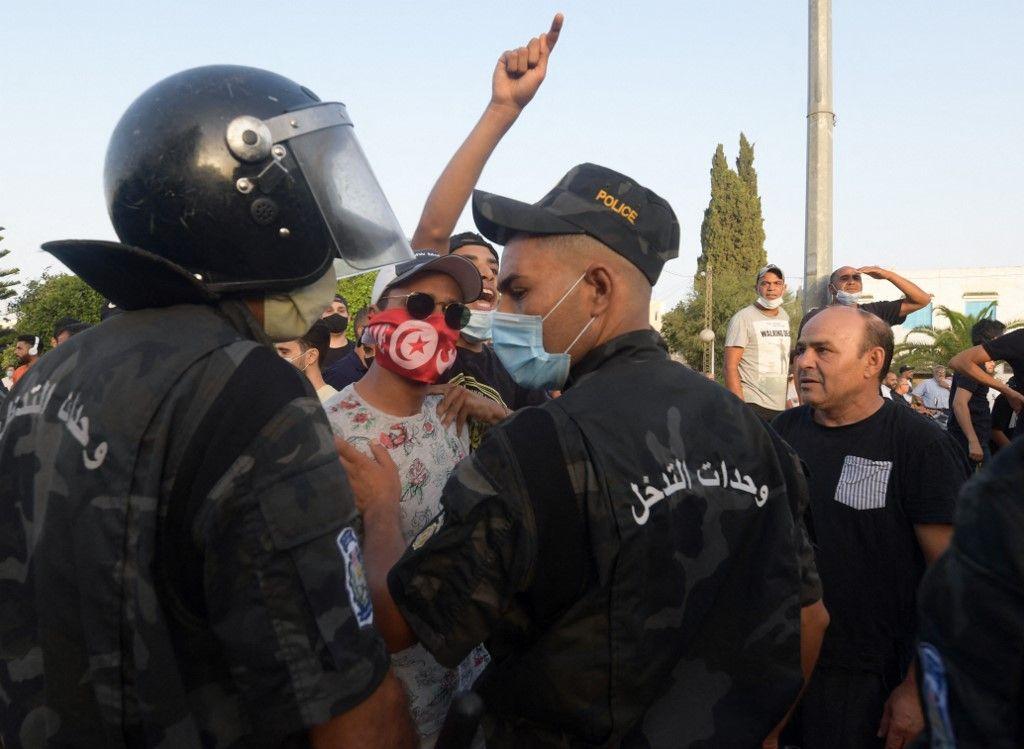 Des agents de sécurité interviennent au milieu des affrontements entre les partisans du président tunisien Kaïs Saïed et les députés du parti Ennahdha devant le Parlement qui a été bouclé à Tunis, le 26 juillet 2021.