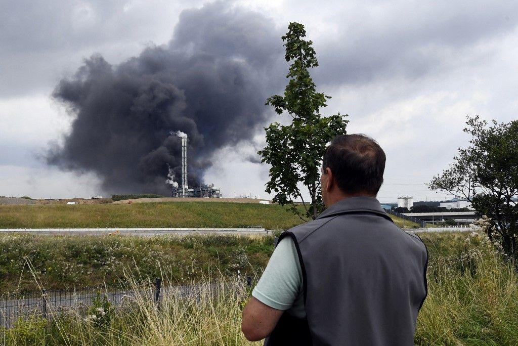 Un homme contemple l'épaisse fumée qui s'élève du site du parc industriel de Chempark géré par l'opérateur Currenta à la suite d'une explosion à Leverkusen, le 27 juillet 2021.