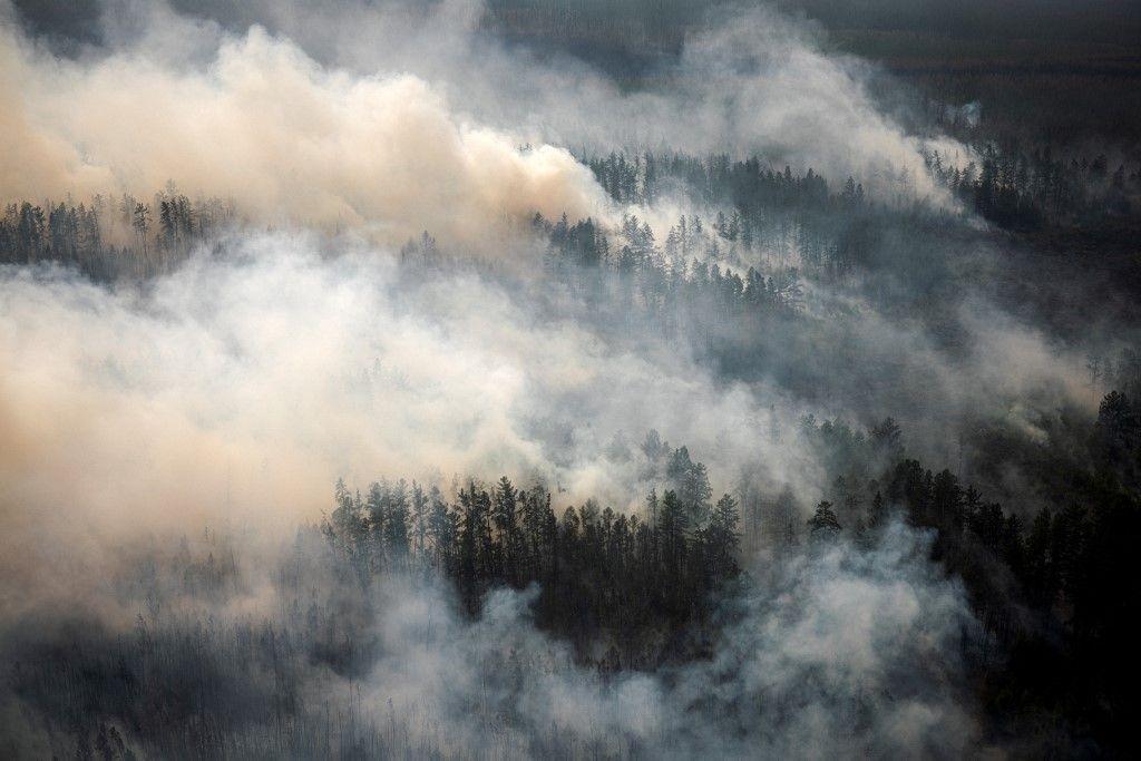 Cette photo aérienne prise depuis un avion le 27 juillet 2021, montre la fumée s'élevant d'un incendie de forêt à l'extérieur du village de Berdigestyakh, dans la république de Sakha, en Sibérie.