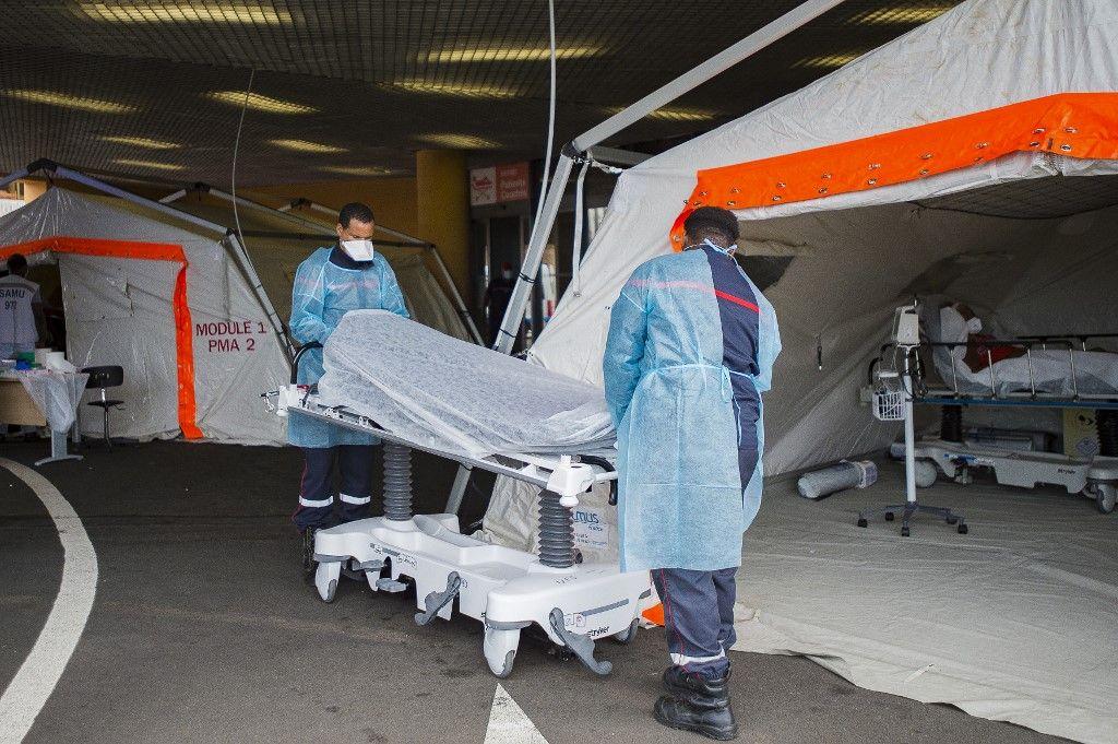 Des pompiers apportent un brancard devant une tente de triage mise en place pour soigner les patients, au centre hospitalier universitaire (CHU) Pierre Zobda-Quitman de Fort-de-France, le 30 juillet 2021.