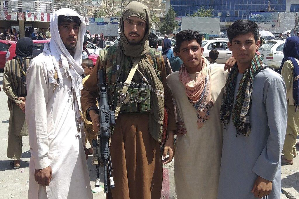 Un combattant taliban est vu avec des habitants à Pul-e-Khumri, le 11 août 2021, après que les talibans aient capturé cette capitale de la province de Baghlan à environ 200 km au nord de Kaboul.