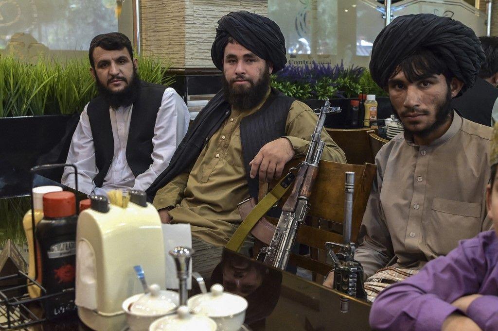 Des combattants talibans attendent que leurs repas soient servis alors qu'ils déjeunent dans un restaurant à Kaboul le 26 août 2021 à la suite du retrait des troupes américaines.